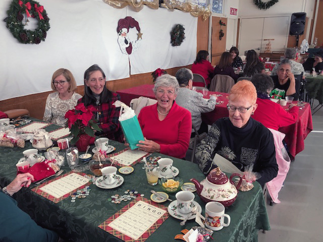 people sitting at table with tea, smiling