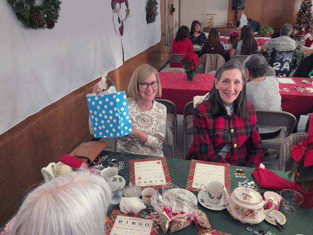 people sitting at table with tea, smiling, one holding up gift bag