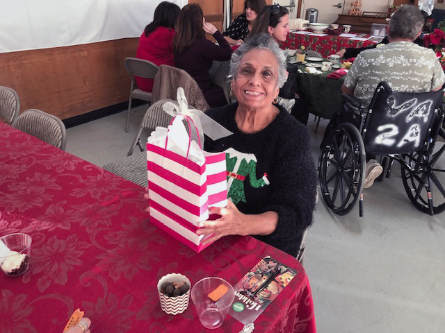 person sitting at table smiling with gift bag