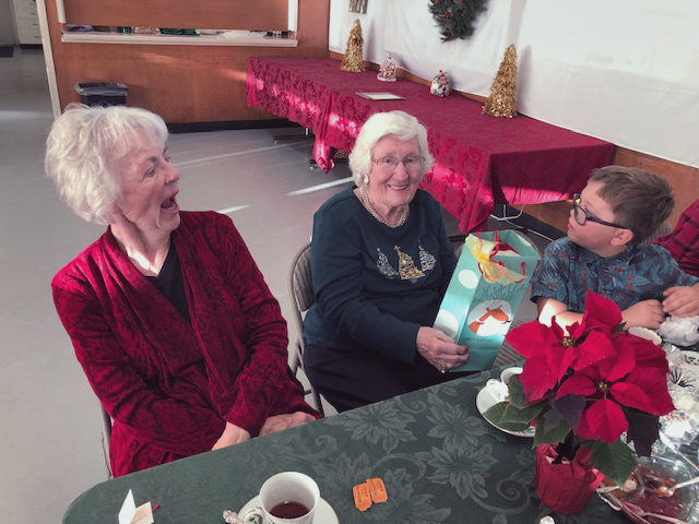 people sitting at table with tea, smiling with gift bag