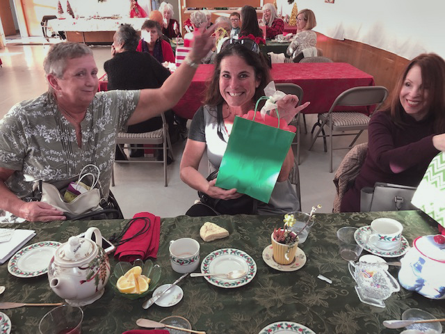 people sitting at table with tea, smiling, one has gift bag
